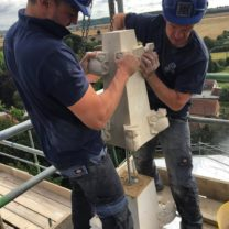 Image showing James one of the Company Directors and Anthony one of our Stonemasons lifting a new Pinnacle into place