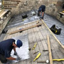 Image showing two of our Lead Workers measuring the Bay lengths ready to boss up and install the new Sandcast lead to the Chancel Roof