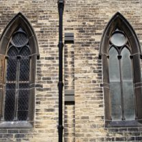 Image of two of the windows at St George, showing the contrast of the new glazing on one window next to the old glass