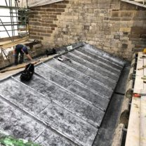 Image showing the new Sandcast Lead being installed to the Chancel roof