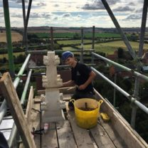 Image showing Tom one of our Apprentices pointing one of the newly fixed Pinnacles